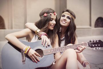 Beautiful stylish friends playing guitar