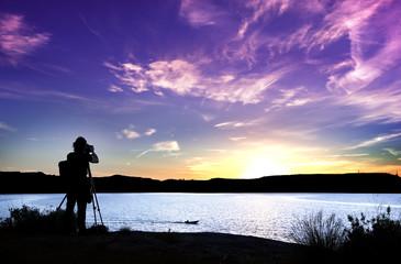 Silueta de fotógrafo con su equipo durante la puesta de sol