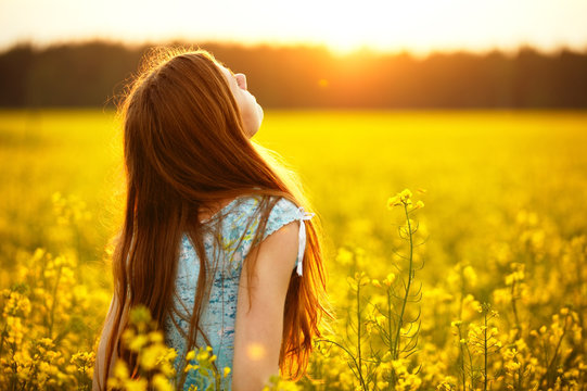 Woman on summer nature in canola field on sunset