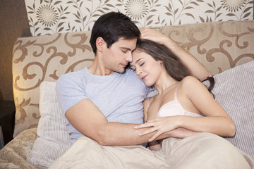 Young couple in love hugging in the bedroom