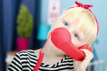 Pretty  little blond girl with a red  retro phone