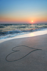 heart outline on beach sand against sea and sunset