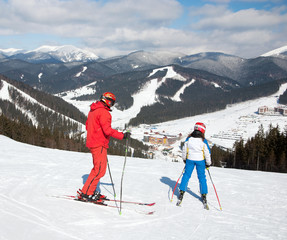 two skiers in red and blue skisuit skiing against snowy mountain