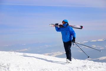 skier in blue skisuit walking against snowy mountains