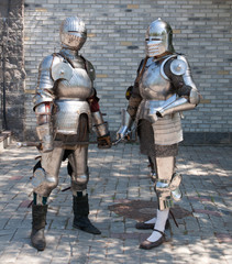 two knights in the ancient metal armor near the wall