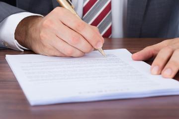 Businessman Signing Document At Desk