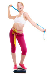 Diet. Fit girl with measure tape on weight scale