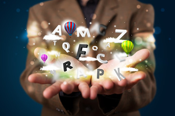 Young businessman presenting magical clouds with letters and bal