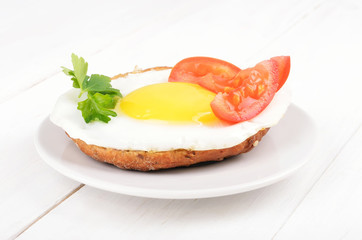 Sandwich with fried egg, tomato slices and parsley