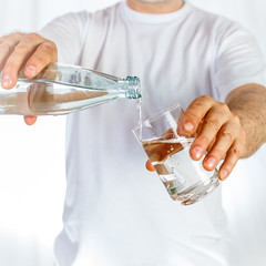Water poured from bottle to glass