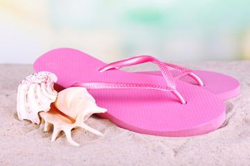 Bright flip-flops on sand, on nature background