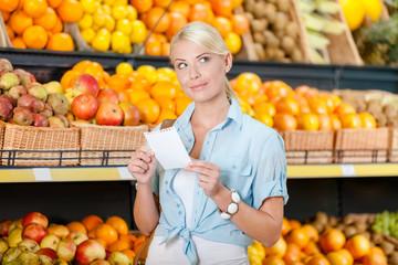 Girl looks through shopping list near the heap of fruits