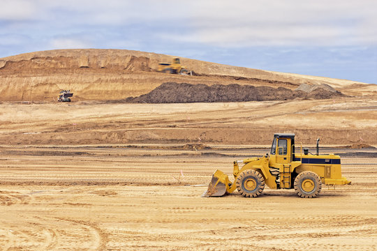Heavy construction loader vehicle at worksite,sky background