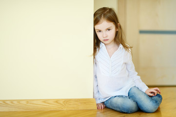 Sad little girl sitting on a floor