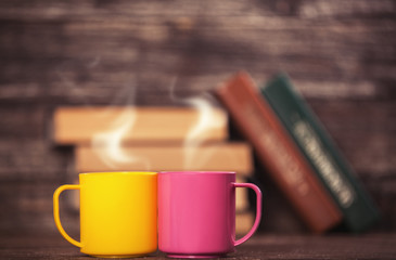 Two cups and books on background.