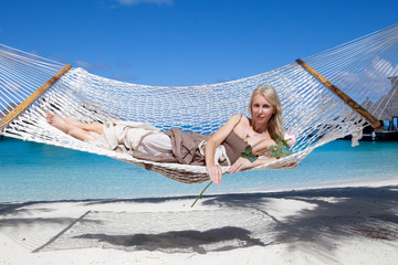 beautiful woman  in a hammock on a sea background..