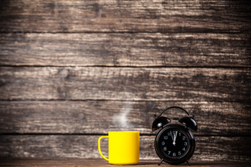 Tea or coffee cup and alarm clock