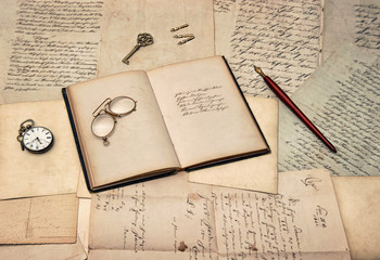 antique writing accessories, open diary book, old letters and po