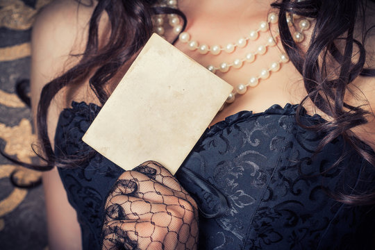 woman wearing black corset and pearls and holding a vintage pape