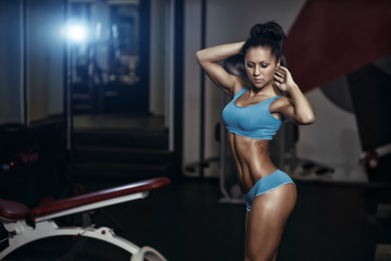 sexy fitness girl with perfect body in the gym posing
