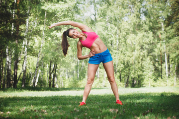 Pretty woman doing sport exercises in the outdoor
