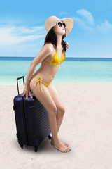 Woman sitting on suitcase at beach
