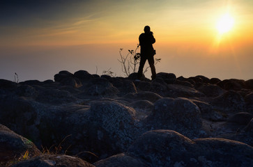 Young man taking photos in the mountains at sunset