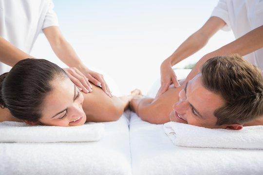 Peaceful couple enjoying couples massage poolside