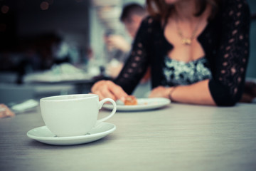 Young woman having coffee and cake