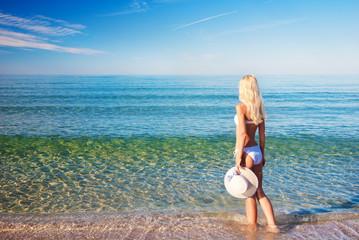 Cute blonde woman in white bikini on sea sand beach