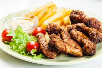 Chicken wings with fries french and spicy sauce