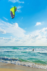 Kitesurfing. Kitesurfer rides the waves against sky
