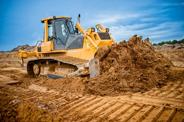 Excavator working with earth and sand in sandpit