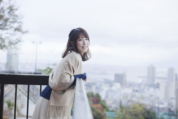 展望台から神戸の景色を望む笑顔の女性