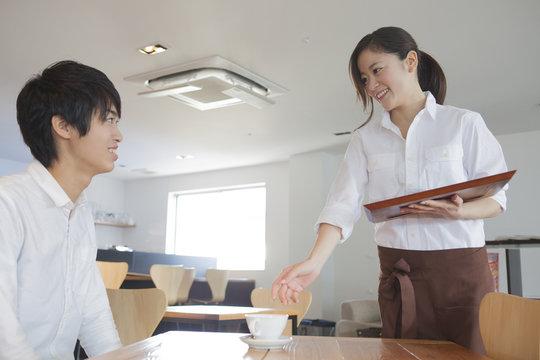 笑顔で接客する女性カフェ店員