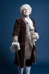 Retro baroque man with white wig standing with walking stick arr