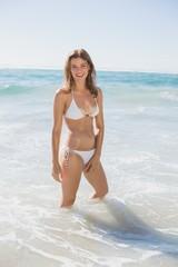 Beautiful smiling woman in white bikini standing in the sea