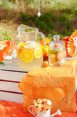 Orange picnic with oranges flowers and glasses of summer