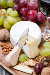 Camembert, a glass of red wine, grapes and crackers