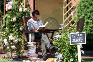"""Schild """"Leselzeit"""" mit lesenden Mann im Garten"""