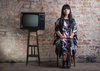 woman and an old television in front of a brick wall.