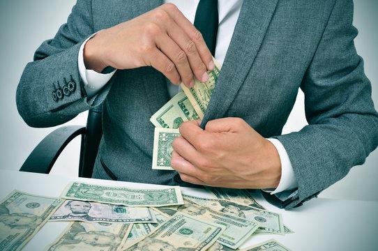 man in suit getting dollar bills in his jacket
