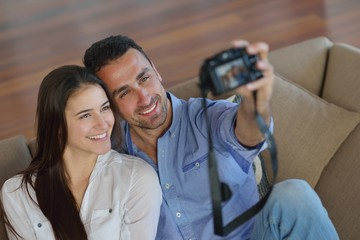 couple playing with digital camera at home