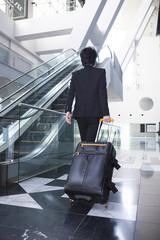 スーツケースを引く男性