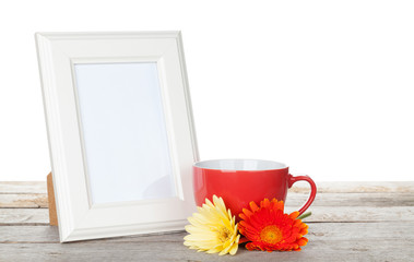 Photo frame with red cup and twocolorful gerbera flowers