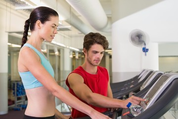 Trainer helping his client set treadmill speed