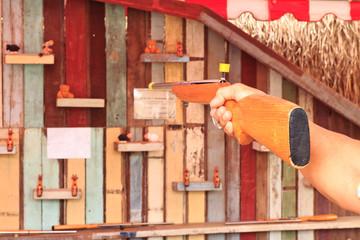 Hold wooden gun aim to doll