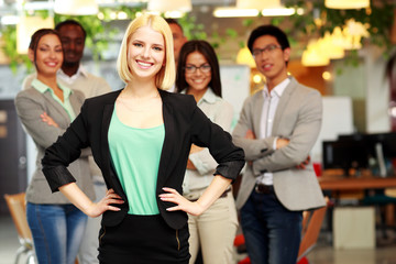 Happy young businesswoman standing