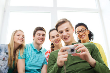 smiling students with digital camera at school