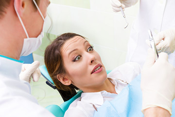 Female patient in dentist office scared, afraid of doctor, proce
